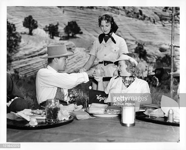 Dennis O'Keefe taking water from a tray next to Virginia Bruce in a scene from the film 'Bad Man Of Brimstone' 1937