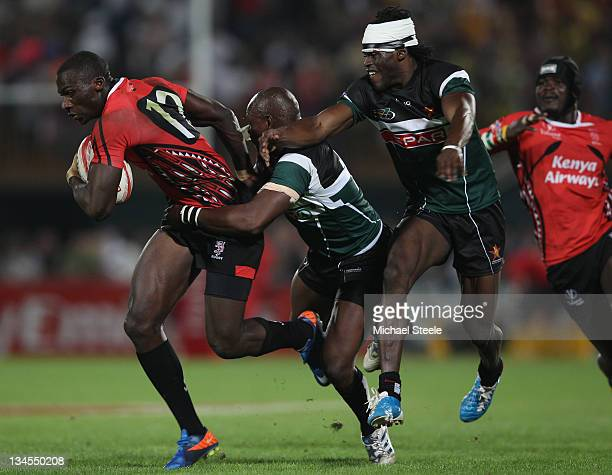 Dennis Ombachi of Kenya holds off Gerald Sibanda and Wensley Mbanje of Zimbabwe during the Kenya v Zimbabwe match on Day Two of the IRB Dubai Sevens...