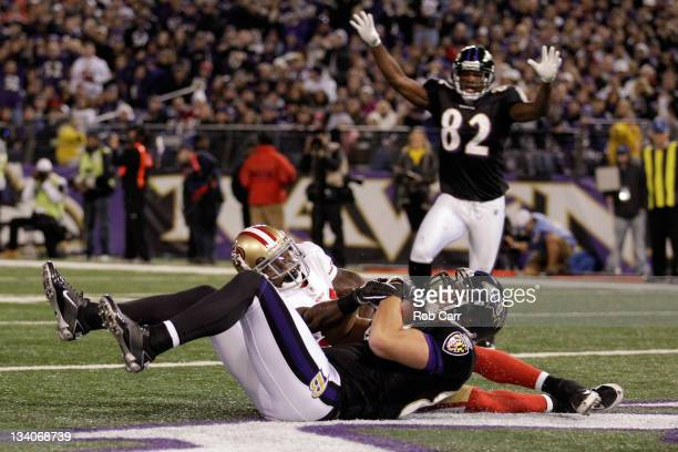 Dennis Pitta of the Baltimore Ravens catches a touchdown pass in front of Donte Whitner of the San Francisco 49ers as Torrey Smith of the Ravens...