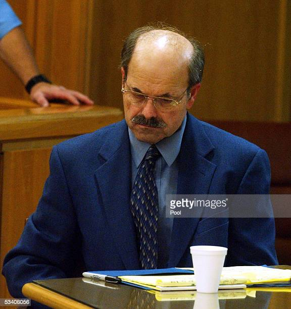 Dennis Rader looks away while pictures of him dressed in women's undergarments are shown at his sentencing hearing August 18 2005 in Wichita Kansas...