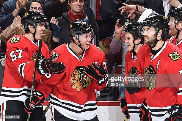 Dennis Rasmussen of the Chicago Blackhawks celebrates with Trevor van Riemsdyk Andrew Shaw and Brent Seabrook after scoring his first NHL goal in the...