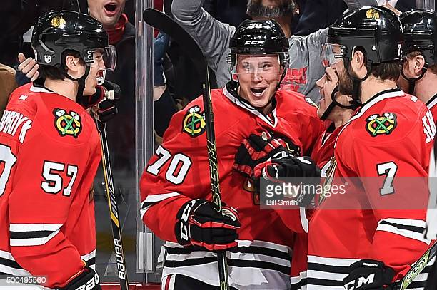 Dennis Rasmussen of the Chicago Blackhawks celebrates with Trevor van Riemsdyk and Brent Seabrook after scoring his first NHL goal in the first...