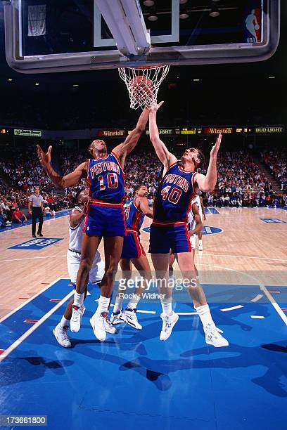 Dennis Rodman and Bill Laimbeer of the Detroit Pistons go up for a rebound against the Sacramento Kings during a game played on December 8 1990 at...