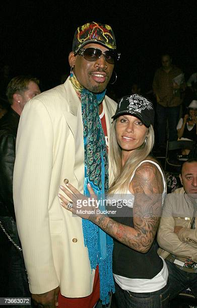 Dennis Rodman and Michelle Moyer pose in the front row at the Christian Audigier Fall 2007 fashion show during Mercedes Benz Fashion Week held at...