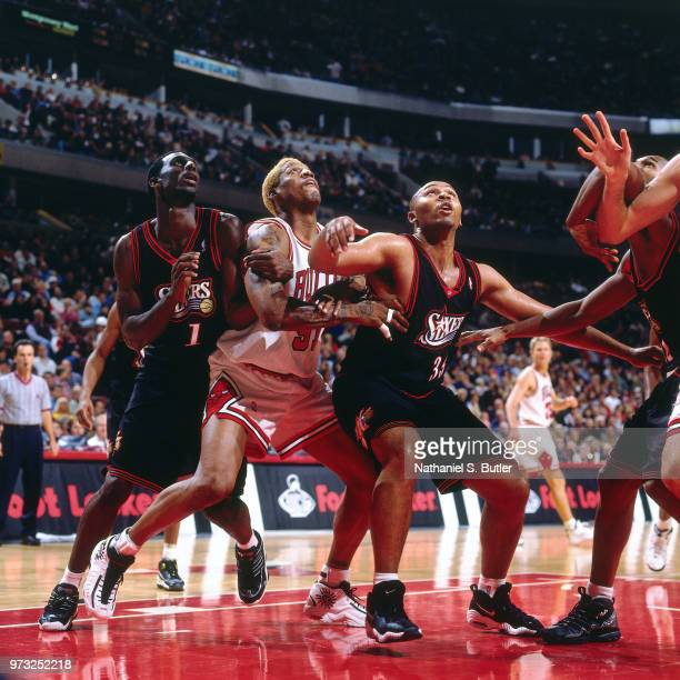 Dennis Rodman battles for a position against Tim Thomas and Clarence Weatherspoon of the Philadelphia 76ers during a game played on November 1 1997...