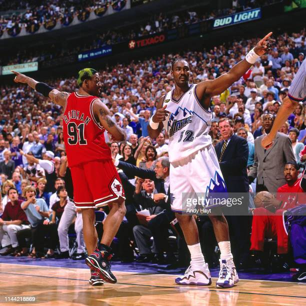 Dennis Rodman of the Chicago Bulls and Karl Malone of the Utah Jazz react to a play during Game Six of the 1998 NBA Finals on June 14 1998 at the...