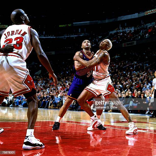 Dennis Rodman of the Chicago Bulls battles against Charles Barkley of the Phoenix Suns during a 1996 NBA game at the United Center in Chicago Ilinois...
