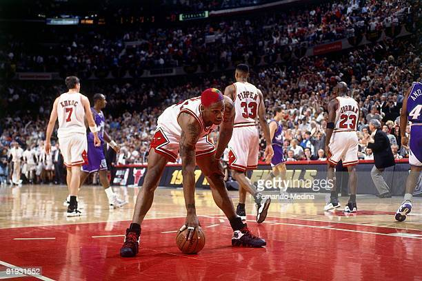 Dennis Rodman of the Chicago Bulls bends down for the ball in Game six of the 1997 NBA Finals against the Utah Jazz at the United Center on June 13...
