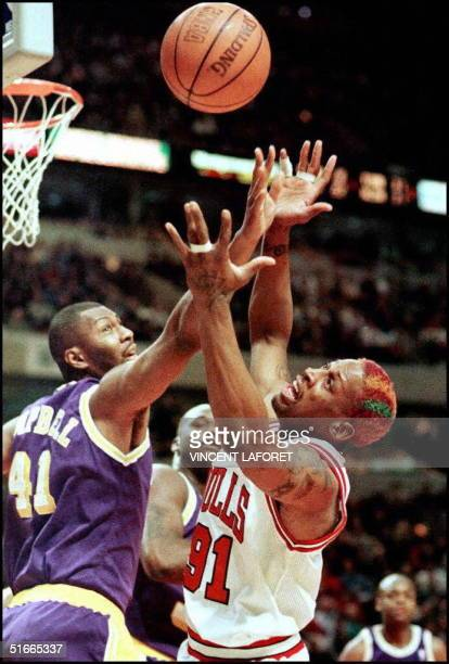 Dennis Rodman of the Chicago Bulls fights Los Angeles Lakers forward Elden Campbell for a rebound as Lakers Shaquille O'Neal looks on in the first...