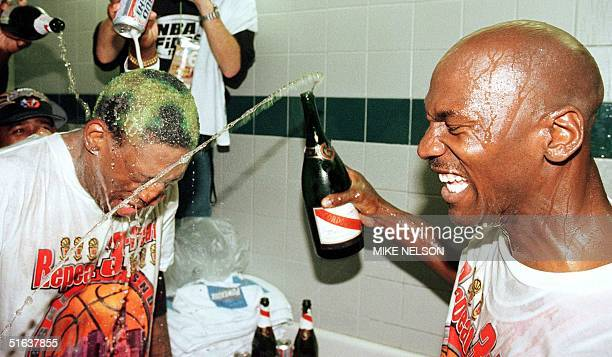 Dennis Rodman of the Chicago Bulls gets beer and champagne poured on his head by teammate Michael Jordan and others 14 June after winning game six of...