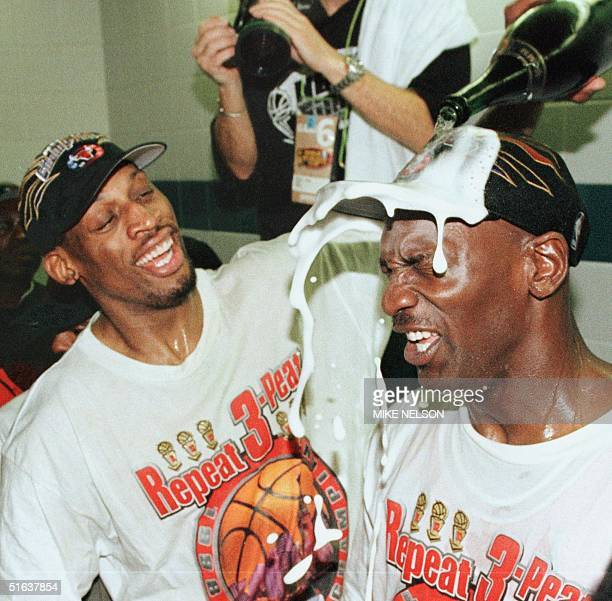 Dennis Rodman of the Chicago Bulls pours champagne on the head of teammate Michael Jordan 14 June after winning game six of the NBA Finals with the...