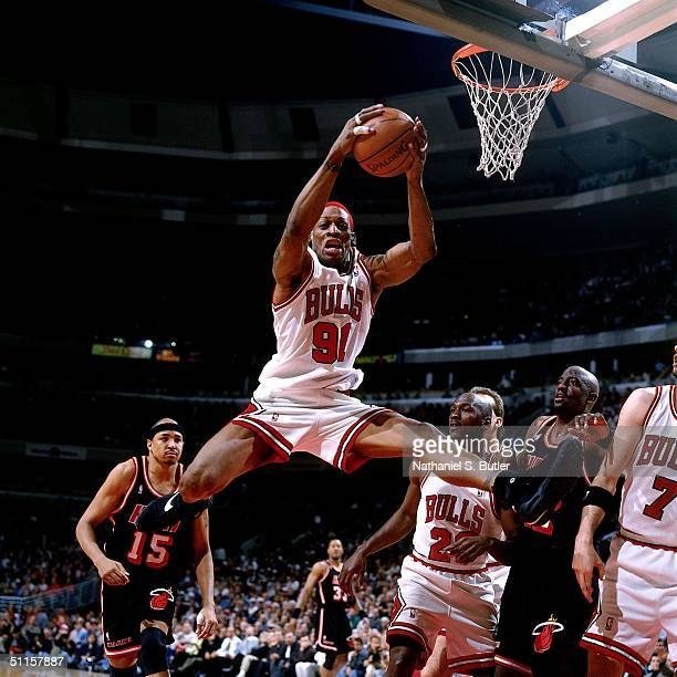Dennis Rodman of the Chicago Bulls rebounds against Chris Gatling of the Miami Heat during a game at The United Center on April 26 1996 in Chicago...