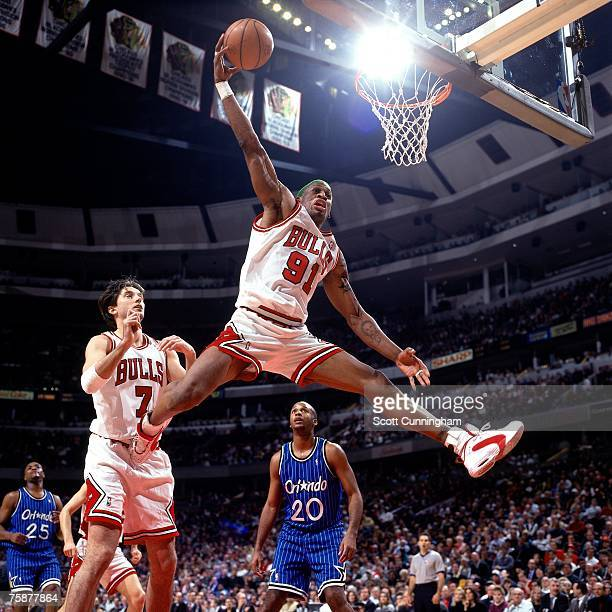 Dennis Rodman of the Chicago Bulls secures a rebound against Brian Shaw of the Orlando Magic during a 1996 NBA game at the United Center in Chicago...