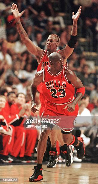 Dennis Rodman of the Chicago Bulls signals a threepoint basket made by teammate Michael Jordan against the Indiana Pacers 29 May during the first...