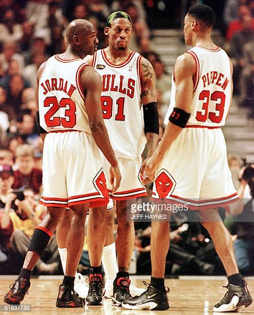 Dennis Rodman of the Chicago Bulls talks to teammates Michael Jordan and Scottie Pippen 10 June during game four of the NBA Finals against the Utah...