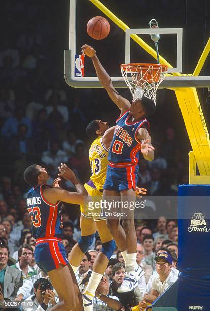 Dennis Rodman of the Detroit Pistons blocks the shot of Mychal Thompson of the Los Angeles Lakers during an NBA basketball game circa 1988 at The...