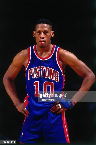 Dennis Rodman of the Detroit Pistons looks on against the Charlotte Hornets during a game played on March 22 1992 at the Charlotte Coliseum in...
