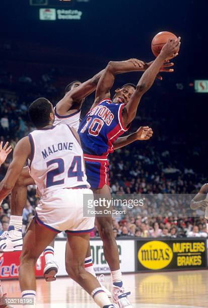 Dennis Rodman of the Detroit Pistons pulls down a rebound in front of Jeff Malone of the Washington Bullets circa 1988 during an NBA basketball game...