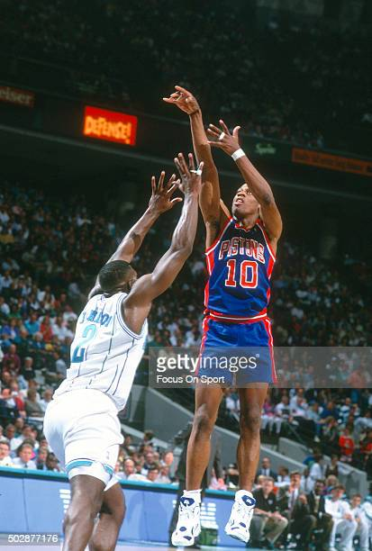 Dennis Rodman of the Detroit Pistons shoots over Larry Johnson of the Charlotte Hornets during an NBA basketball game circa 1993 at the Charlotte...