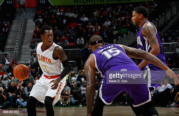 Dennis Schroder of the Atlanta Hawks against DeMarcus Cousins and Rudy Gay of the Sacramento Kings at Philips Arena on November 18 2015 in Atlanta...