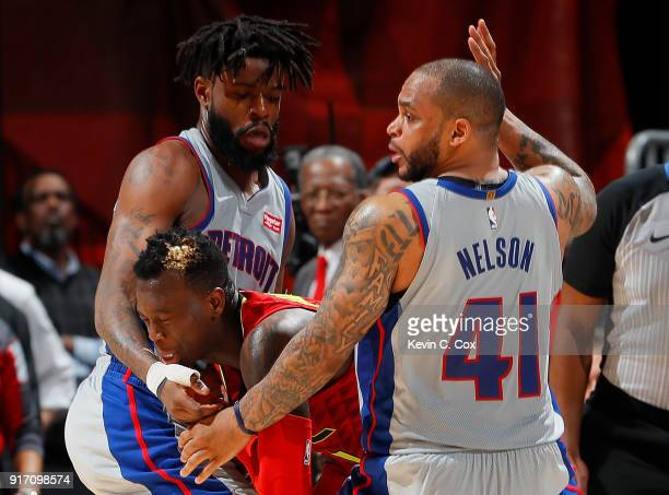 Dennis Schroder of the Atlanta Hawks draws a foul as he is trapped by Reggie Bullock and Jameer Nelson of the Detroit Pistons at Philips Arena on...