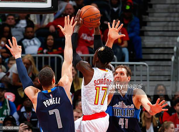 Dennis Schroder of the Atlanta Hawks draws a foul from Dwight Powell of the Dallas Mavericks as he drives against Powell and Dirk Nowitzki at Philips...
