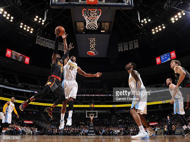 Dennis Schroder of the Atlanta Hawks drives to the basket and gets his shot blocked by Darrell Arthur of the Denver Nuggets on January 25 2016 at the...
