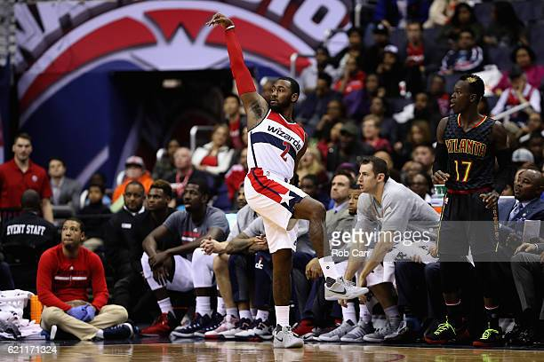 Dennis Schroder of the Atlanta Hawks looks on as John Wall of the Washington Wizards follows his shot in the second half at Verizon Center on...