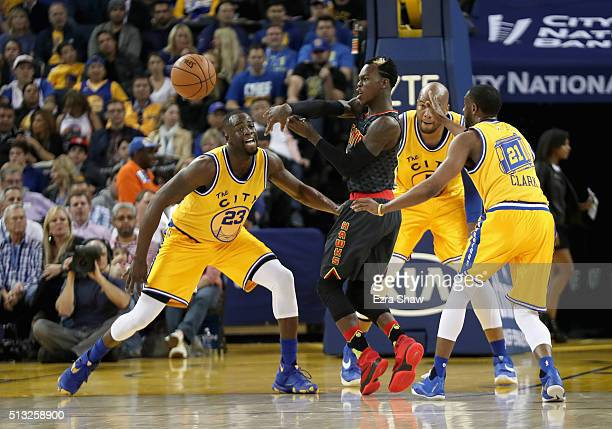 Dennis Schroder of the Atlanta Hawks passes the ball while covered by Draymond Green Marreese Speights and Ian Clark of the Golden State Warriors at...