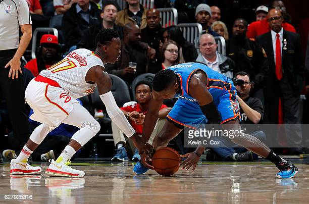 Dennis Schroder of the Atlanta Hawks reaches for a steal against Victor Oladipo of the Oklahoma City Thunder at Philips Arena on December 5 2016 in...