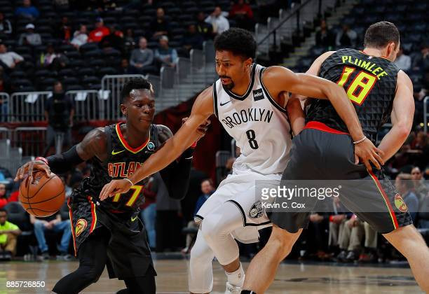 Dennis Schroder of the Atlanta Hawks runs around a screen by Miles Plumlee against Spencer Dinwiddie of the Brooklyn Nets at Philips Arena on...