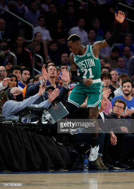 Dennis Schroder of the Boston Celtics crashes into fans as he leaps to keep a ball inbounds during the first half against the New York Knicks at...