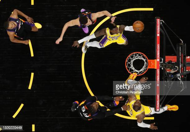 Dennis Schroder of the Los Angeles Lakers lays up a shot past Devin Booker of the Phoenix Suns during Game Two of the Western Conference first-round...