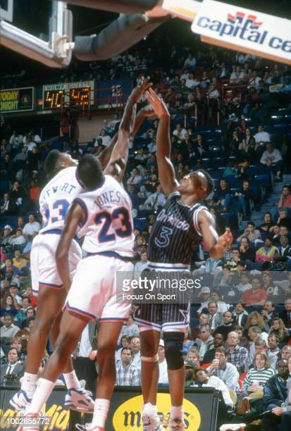 Dennis Scott of the Orlando Magic shoots over Larry Stewart and Charles Jones of the Washington Bullets during an NBA basketball game circa 1991 at...