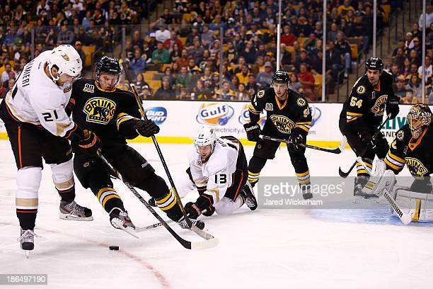 Dennis Seidenberg of the Boston Bruins is tripped up by Nick Bonino of the Anaheim Ducks in front of the puck in the second period at TD Garden on...