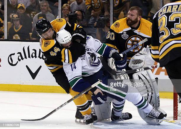 Dennis Seidenberg of the Boston Bruins tackles Alex Burrows of the Vancouver Canucks after an incident with Tim Thomas of the Boston Bruins during...