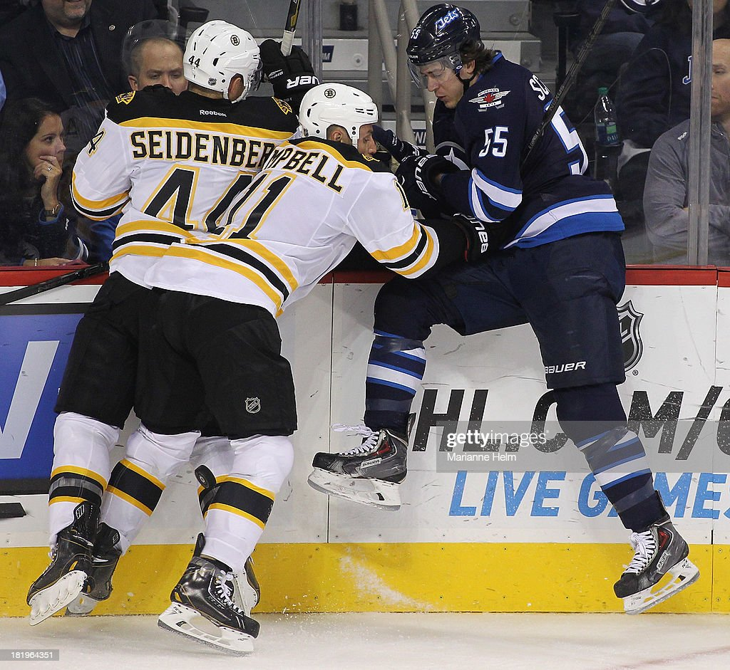 Dennis Seidenberg #44 of the Boston Bruins teams up with Gregory Campbell #11 to stop Mark Scheifele #55 of the Winnipeg Jets along the boards in third period action during an NHL preseason game at the MTS Centre on September 26, 2013 in Winnipeg, Manitoba, Canada.