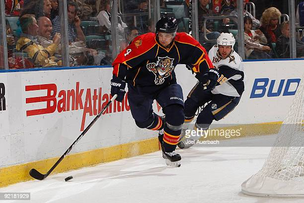 Dennis Seidenberg of the Florida Panthers skates with the puck behind the net trailed by Tim Connolly of the Buffalo Sabres in the second period on...