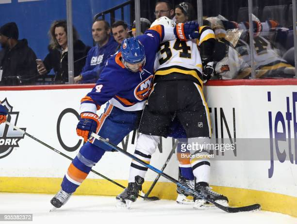 Dennis Seidenberg of the New York Islanders checks Tom Kuhnhackl of the Pittsburgh Penguins during the first period at the Barclays Center on March...