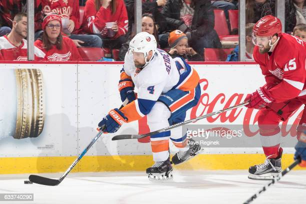 Dennis Seidenberg of the New York Islanders skates with the puck followed by Riley Sheahan of the Detroit Red Wings during an NHL game at Joe Louis...