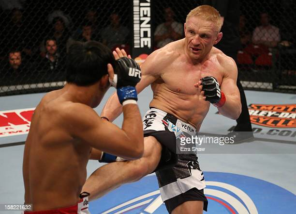 Dennis Siver kicks Nam Phan during their featherweight bout at the UFC on FOX event on December 8, 2012 at Key Arena in Seattle, Washington.
