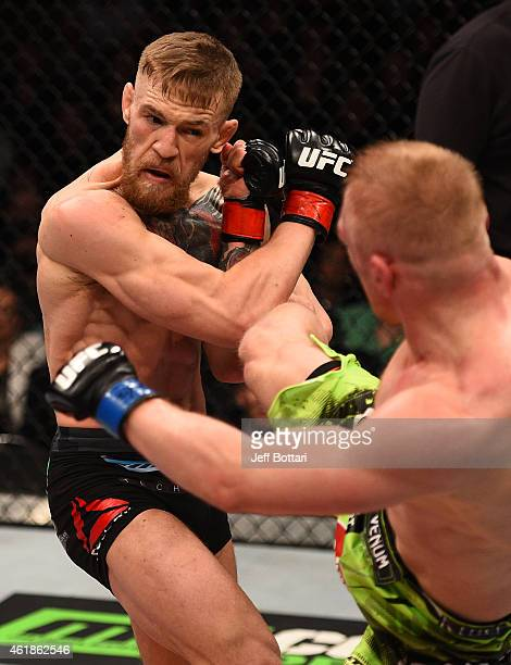 Dennis Siver of Germany kicks Conor McGregor of Ireland in their featherweight fight during the UFC Fight Night event at the TD Garden on January 18...