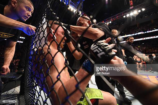 Dennis Siver of Germany receives treatment during a featherweight fight against Conor McGregor of Ireland during the UFC Fight Night event at the TD...