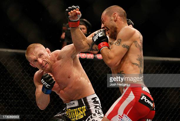 Dennis Siver punches Cub Swanson in their featherweight fight during the UFC 162 event inside the MGM Grand Garden Arena on July 6, 2013 in Las...