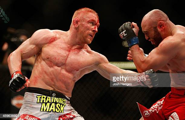 Dennis Siver punches Manny Gamburyan in their featherweight bout during the UFC 168 event at the MGM Grand Garden Arena on December 28 2013 in Las...