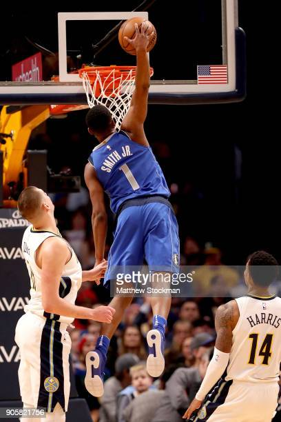 Dennis Smith Jr #1 of the Dallas Mavaricks dunks against Nikola Jokic and Gary Harris of the Denver Nuggets at the Pepsi Center on January 16 2018 in...