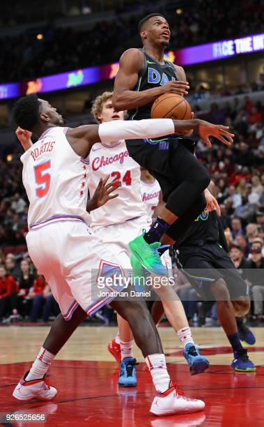 Dennis Smith Jr #1 of the Dallas Mavericks drives between Bobby Portis and Lauri Markkanen of the Chicago Bulls at the United Center on March 2 2018...