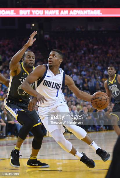 Dennis Smith Jr #1 of the Dallas Mavericks drives towards the basket on Andre Iguodala of the Golden State Warriors during an NBA basketball game at...