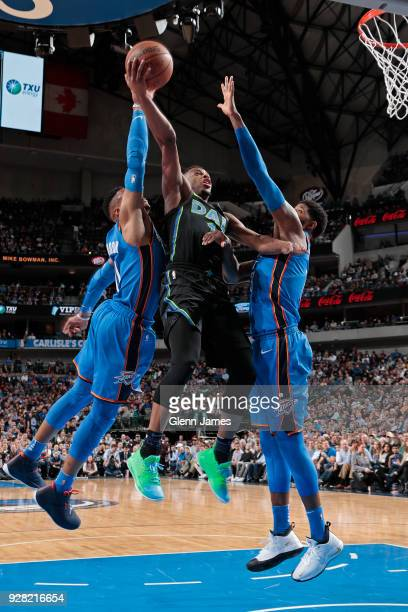 Dennis Smith Jr #1 of the Dallas Mavericks shoots the ball inbetween Russell Westbrook and Paul George of the Oklahoma City Thunderduring the game...