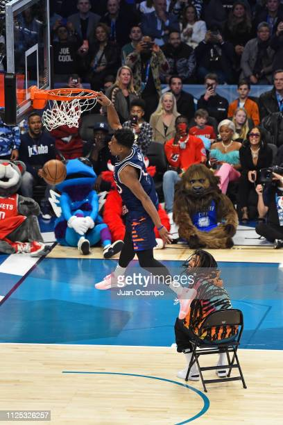Dennis Smith Jr #5 of the New York Knicks dunks the ball over Rapper J Cole during the 2019 ATT Slam Dunk Conest on February 16 2019 at the Spectrum...